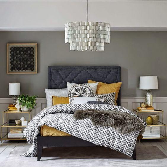 une chambre brillante et élégante avec des murs gris, des boiseries blanches, un lit gris graphite, un lustre brillant, des tables de chevet à cadre doré et une literie moutarde