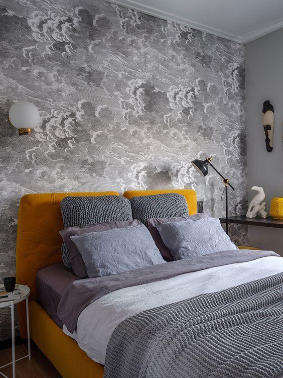 une petite chambre avec un mur de papier peint nuage gris, un lit rembourré moutarde et des accessoires, une literie grise et blanche
