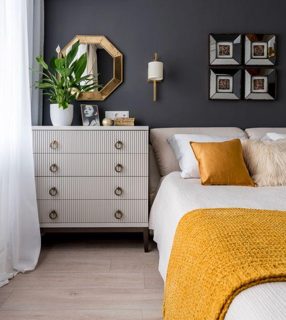 une élégante chambre moderne du milieu du siècle avec des murs gris graphite, des meubles neutres, des touches brillantes et lumineuses et une literie jaune et blanche