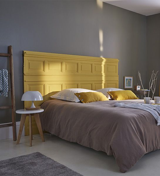 une chambre éclectique aux murs gris, un lit lambrissé jaune, une literie grise et moutarde est très rêveuse