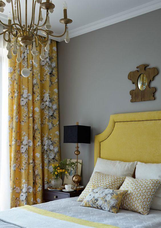 une chambre élégante d'inspiration vintage avec des murs gris clair, un lit moutarde, des rideaux fleuris moutarde, un lustre chic et une literie grise et moutarde