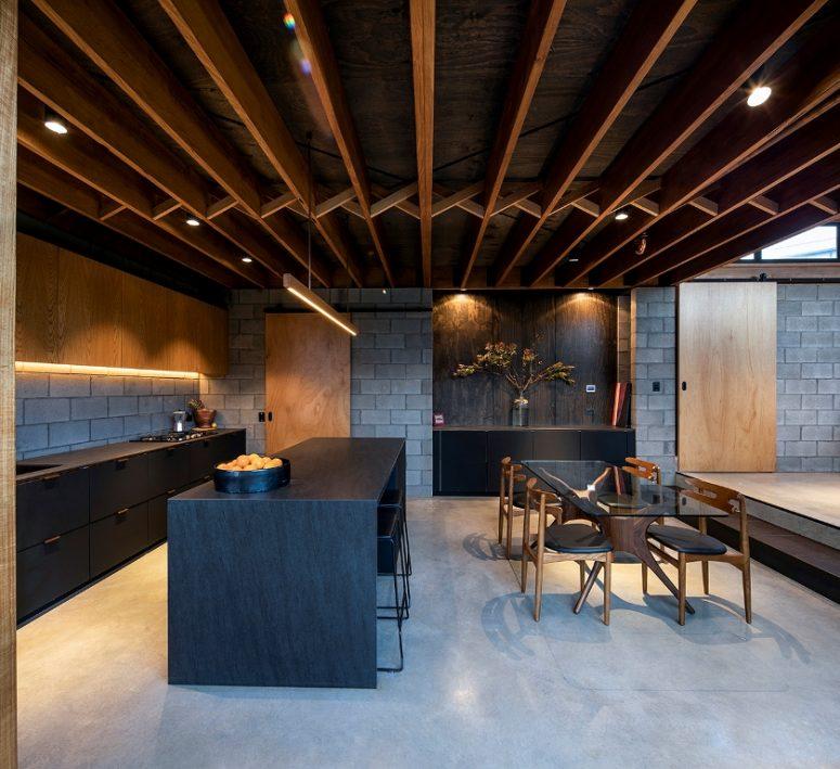 La cuisine est faite avec des meubles en béton, teinté clair et noir mat, un îlot de cuisine noir et l'espace salle à manger comprend une belle table en verre