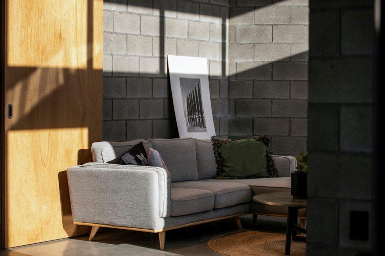 Un tapis de jute, des murs en béton, une table en métal rendent l'espace plus accrocheur avec des textures et plus accueillant