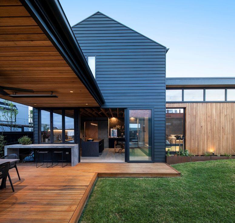 La maison présente une cuisine et un espace salle à manger qui peuvent être ouverts sur l'extérieur avec des portes coulissantes et une zone de repas supplémentaire à l'extérieur mais sous un toit