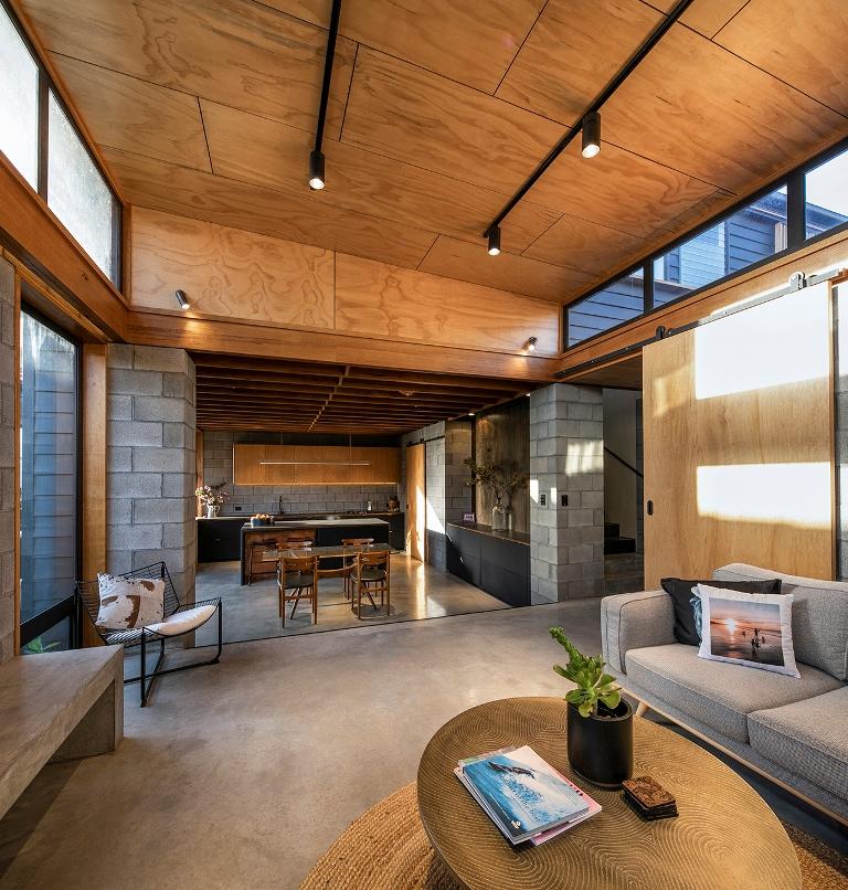 La cuisine s'ouvre sur un salon, avec des meubles confortables et neutres, un sol en béton et des murs vitrés