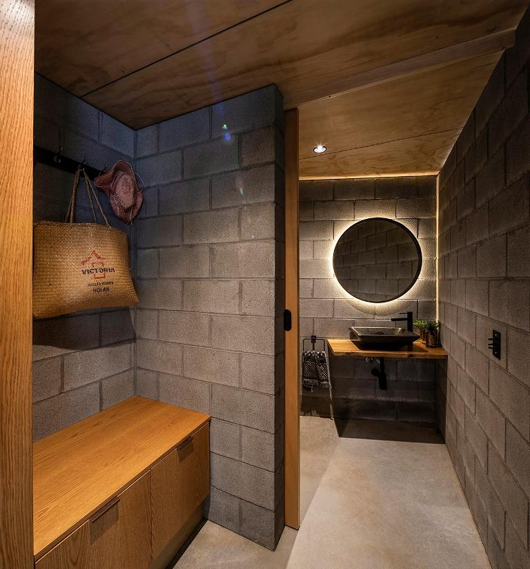 La salle de bain continue le thème de la décoration avec des murs et des sols en béton, un miroir éclairé et du bois teinté neutre