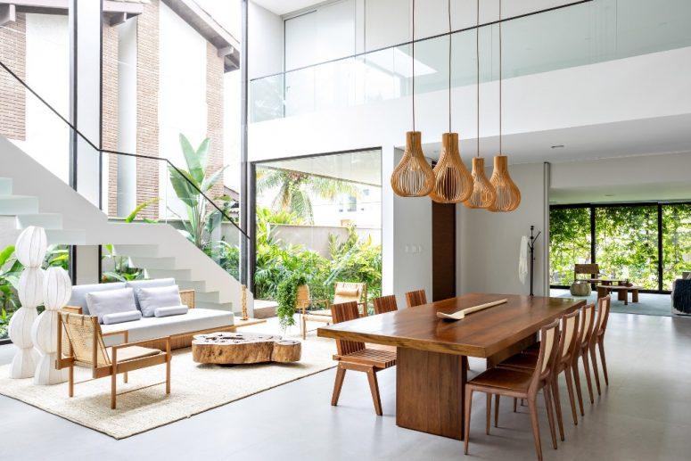 Les espaces de vie et de salle à manger sont réunis en une seule disposition, avec un mobilier chic et un vaste vitrage pour apporter autant de lumière que possible à l'intérieur