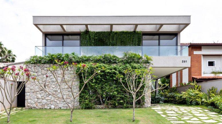 Il y a beaucoup de verdure autour et sur la maison et un grand balcon minimaliste