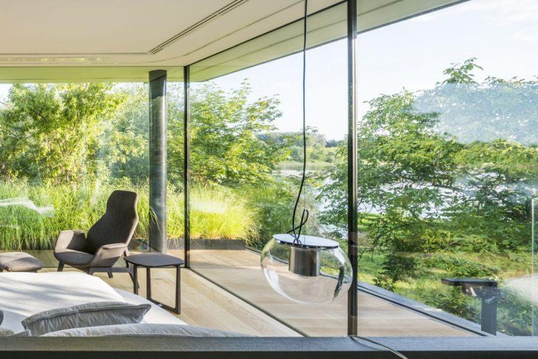 De grandes baies vitrées et des murs en verre révèlent la vue magnifique sur la rivière