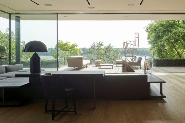 Le salon est aménagé avec un mobilier confortable gris et noir et peut être ouvert sur une terrasse extérieure