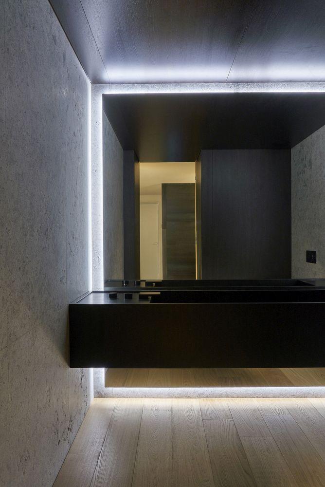 La salle de bain est minimaliste, avec une vanité flottante noire, un mur de miroir et des lumières intégrées