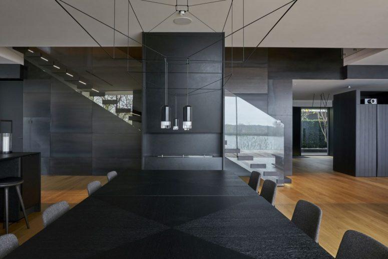 La cuisine et la salle à manger sont en noir, avec des lampes contemporaines et un design audacieux