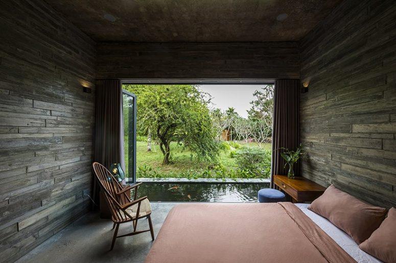 La chambre est dotée de panneaux de béton Woodgran la recouvrant complètement, d'un mur vitré qui peut être ouvert comme une porte vers l'étang et de meubles confortables pour dormir