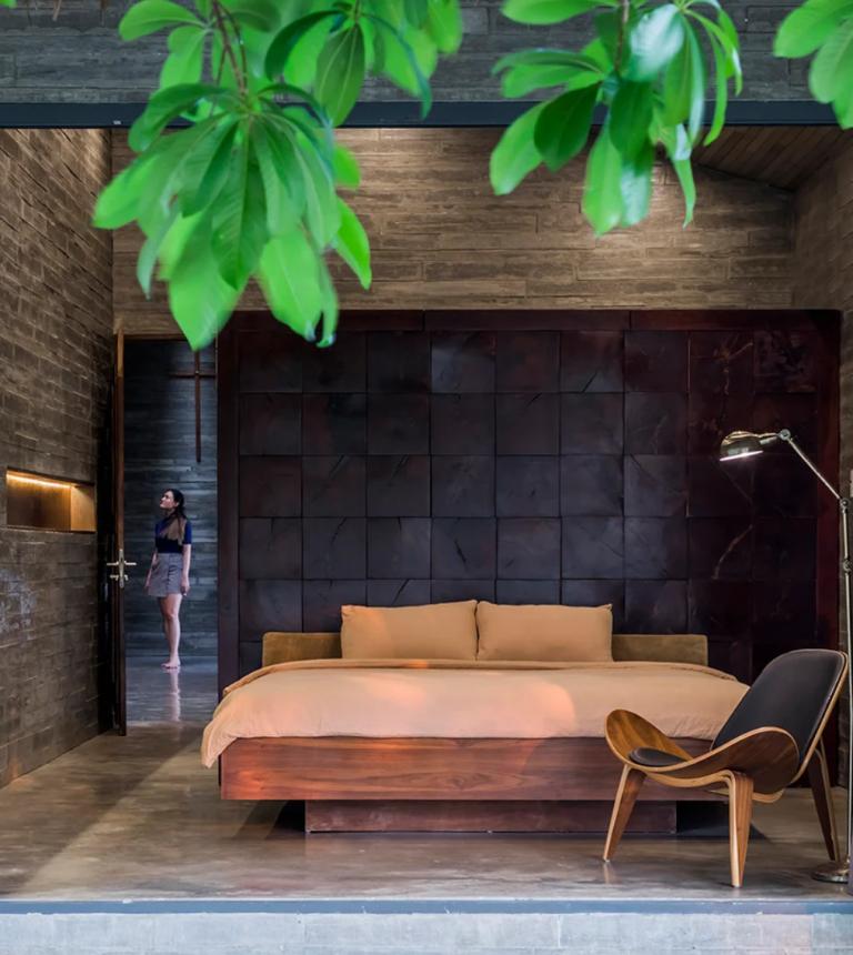La chambre présente des panneaux de béton en similibois, un magnifique mur teinté en bois et des meubles en bois chics