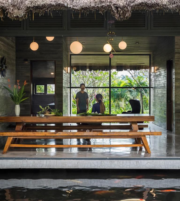 L'espace salle à manger intérieur est fait avec des bancs et une longue table et peut également être complètement ouvert sur l'étang