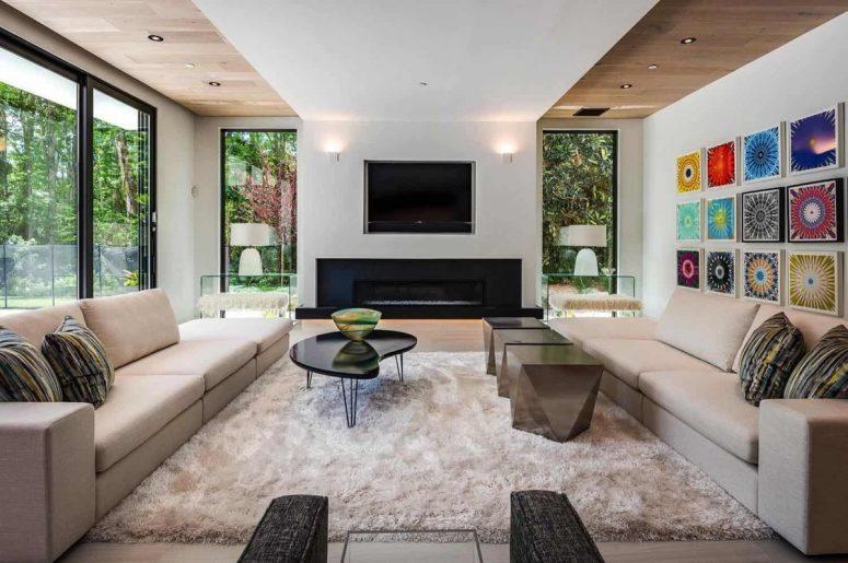 Le salon est fait avec de vastes vitrages, une cheminée intégrée, un mobilier élégant et des tapis