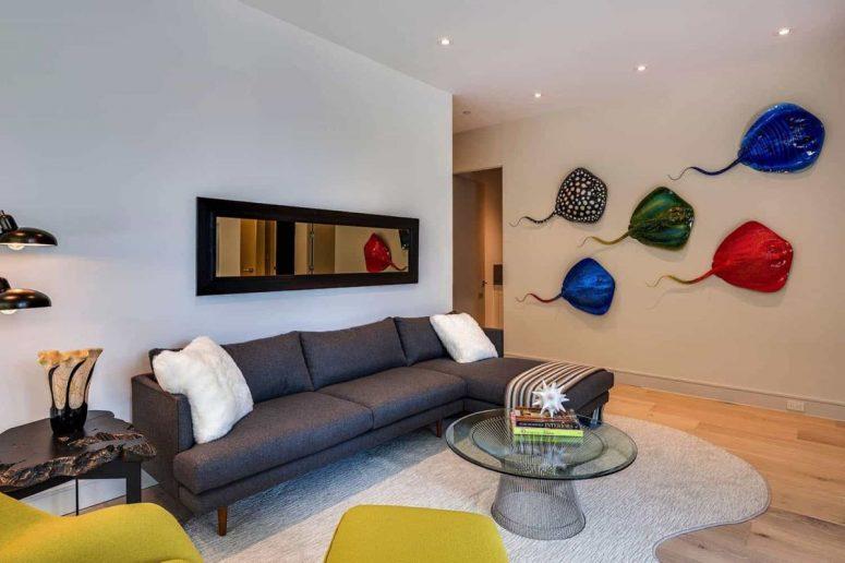 Un deuxième mini salon est fait avec des meubles élégants, des pièces de moutarde brillantes et des œuvres d'art colorées sur le mur
