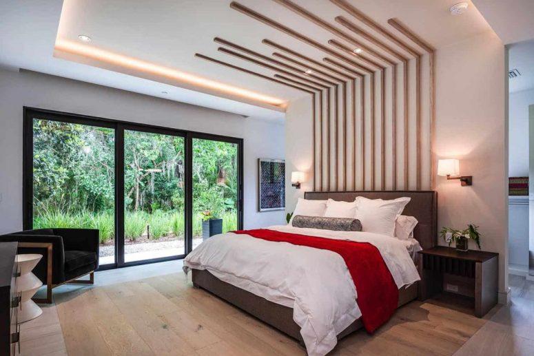 Une autre chambre présente une tête de lit allongée fraîche, beaucoup de lumière et un mur vitré