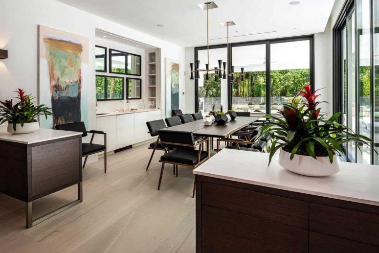 La salle à manger est également lumineuse, avec des meubles sombres élégants, des lampes noires et des œuvres d'art audacieuses