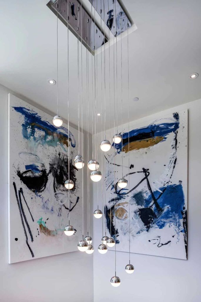 L'espace de l'escalier est agrémenté d'œuvres d'art lumineuses et de lampes suspendues à bulles