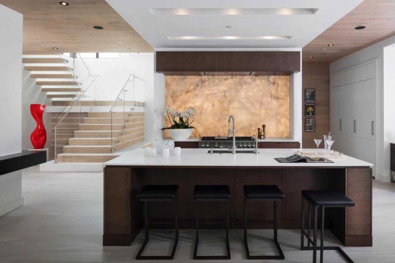 La cuisine est faite avec des meubles teintés foncés, des comptoirs en pierre blanche et un magnifique dosseret rétroéclairé en quartzite