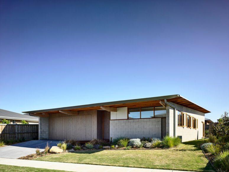 La maison dispose d'un étage et est vêtue de tons neutres, le paysage correspond parfaitement