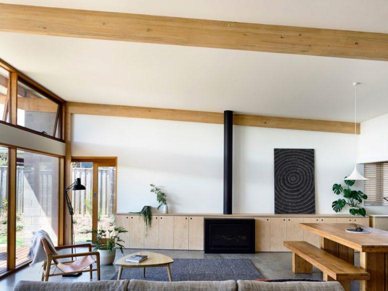 Le salon comprend de vastes vitrages, des armoires en contreplaqué pour le rangement, une cheminée, des meubles confortables et un espace salle à manger ici
