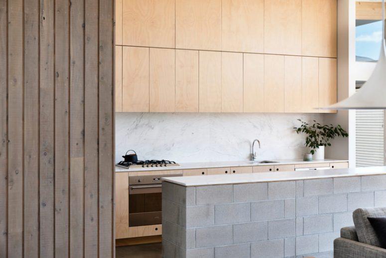 Les armoires en contreplaqué correspondent parfaitement à celles de la zone du salon et rendent l'espace cohérent