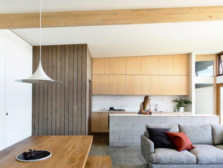 La cuisine est faite avec des armoires en contreplaqué, un dosseret en marbre et un îlot de cuisine carrelé avec un comptoir en pierre