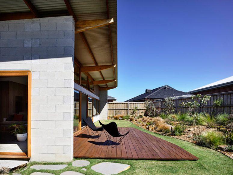 Il y a une terrasse confortable avec un aménagement paysager élégant