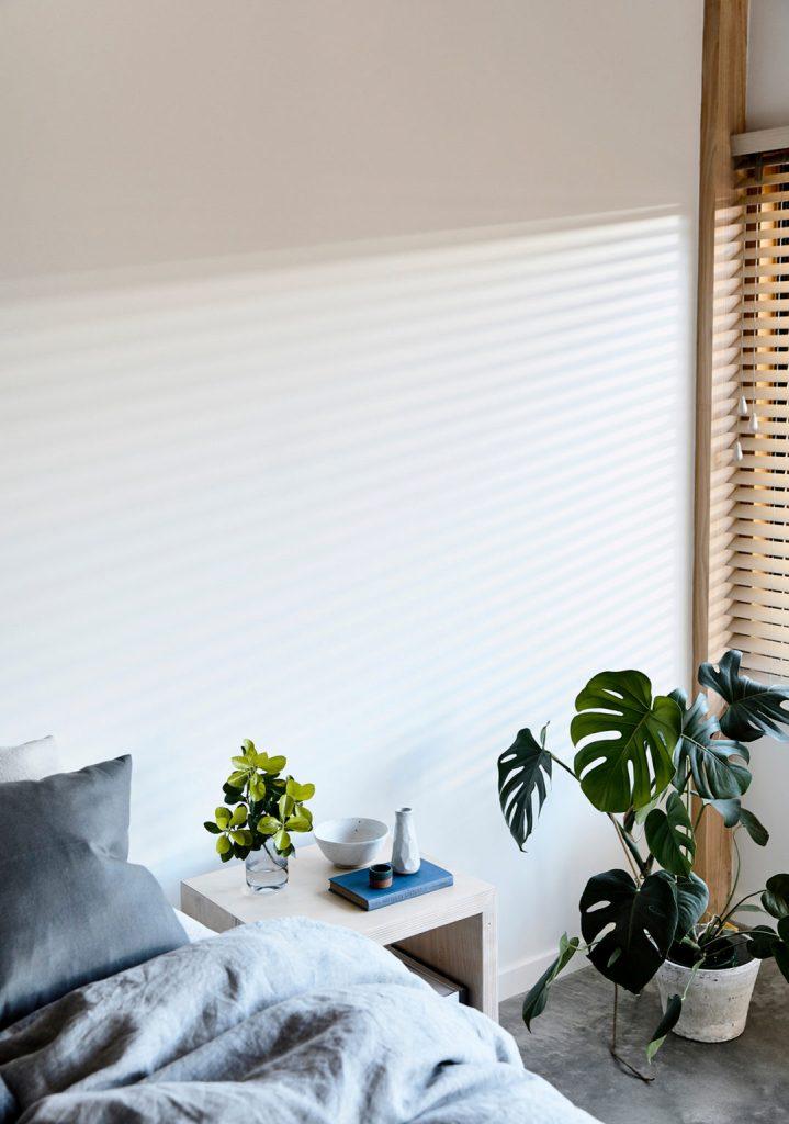La chambre est entièrement neutre, avec des murs blancs et un sol en béton, des meubles simples mais élégants et de la verdure en pot