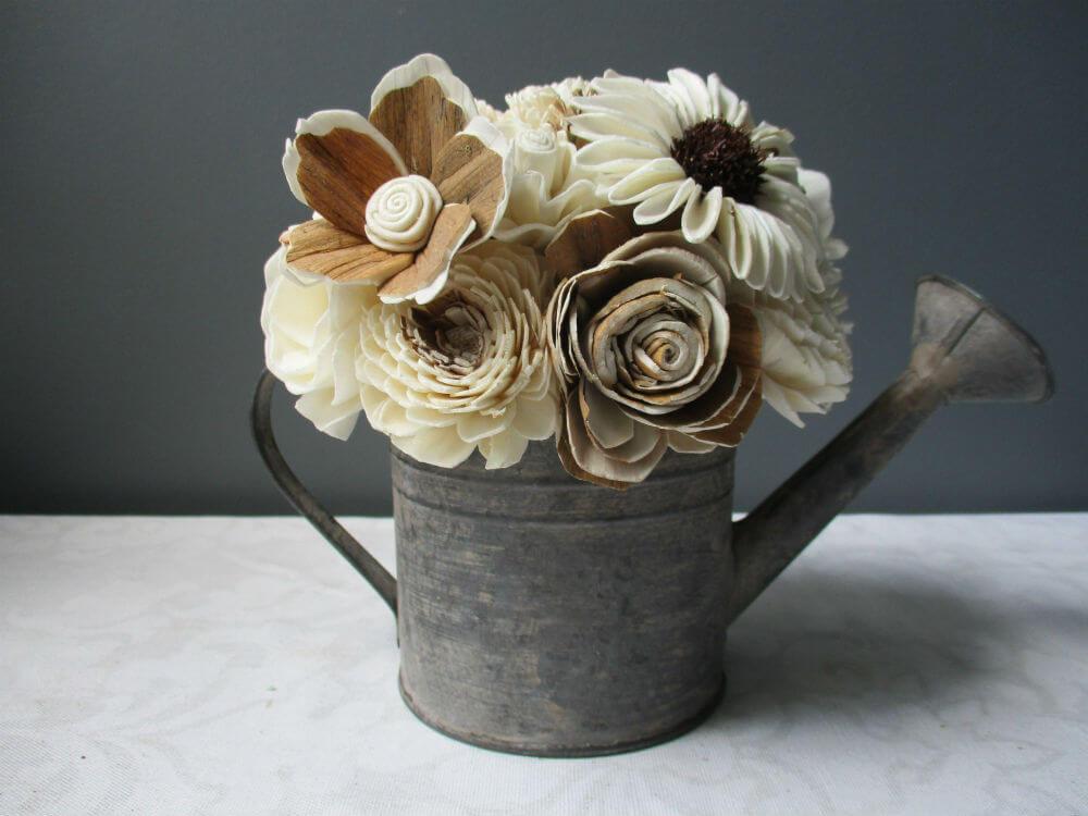 Arrosoir de ferme débordant avec des fleurs de Sola