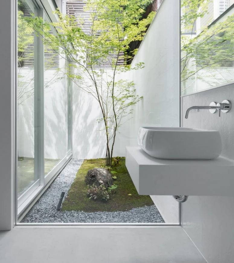 Les salles de bains ont des murs vitrés qui mènent à une cour intérieure avec des rochers et des arbres - une fusion de la nature et du design moderne