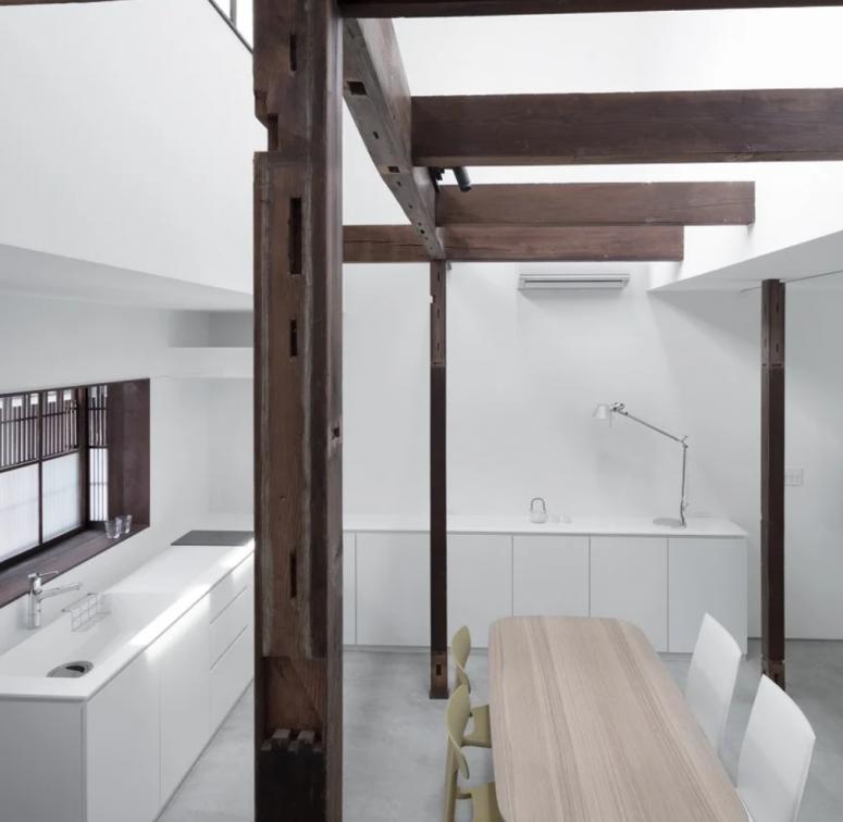 La cuisine est blanche et minimaliste, et l'espace salle à manger est également ici, la structure en bois d'origine ajoute de l'intérêt à l'espace