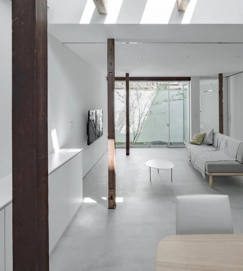 Le salon est également neutre et minimaliste, les poutres en bois teintées foncées ajoutent du chic à l'espace et les puits de lumière apportent l'extérieur à l'intérieur