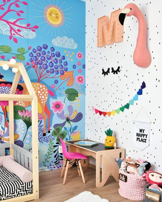 une chambre d'enfant belle et audacieuse avec un mur peint brillant, une fausse taxidermie, des guirlandes et des jouets audacieux et une chaise rose vif