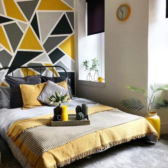 une chambre moderne et audacieuse avec des murs gris tourterelle, un lit forgé noir, une literie grise et jaune et un mur géométrique gris et moutarde