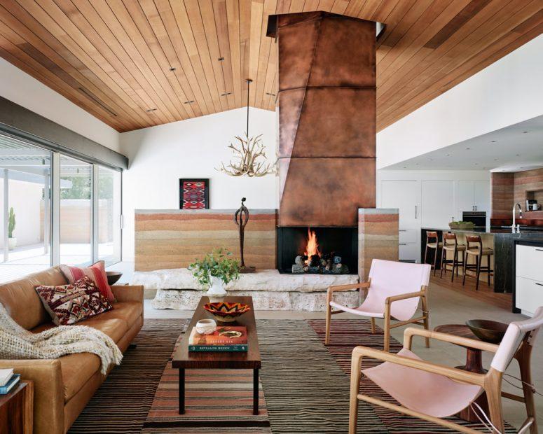 Le salon présente une magnifique cheminée revêtue de cuivre sur pierre, des meubles élégants et des tapis en couches