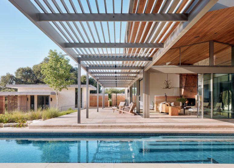 Il y a un toit de pergola qui prolonge le salon à l'extérieur jusqu'à la piscine