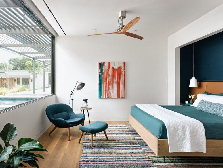 La chambre principale est faite en blanc et bleu sarcelle, elle offre une vue fraîche sur les espaces extérieurs