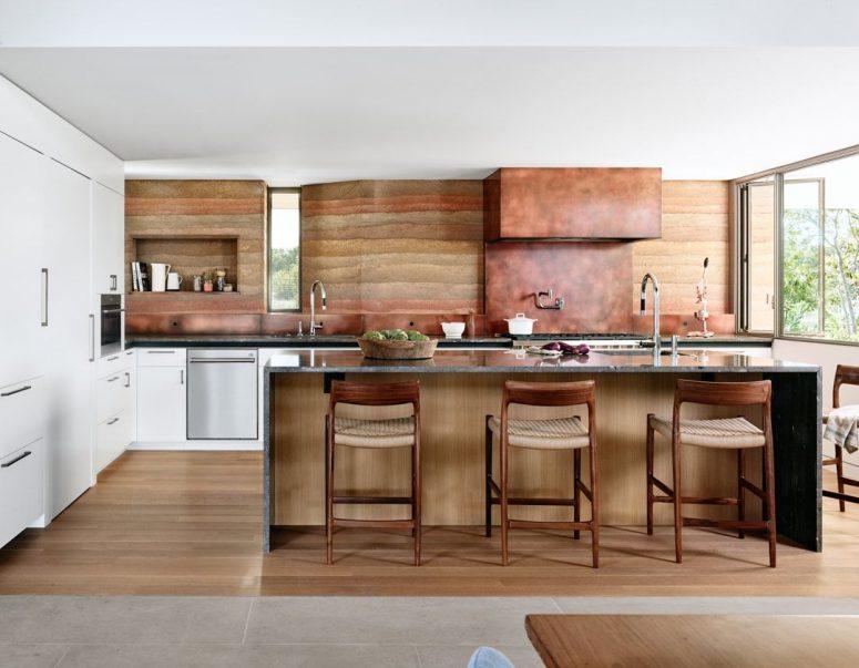 Le backspalsh et la hotte sont revêtus de cuivre pour faire écho à la cheminée et mettre en évidence la palette de couleurs