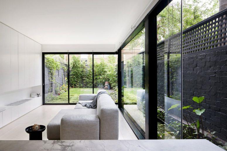 Le salon dispose de vastes vitrages, d'un meuble de rangement blanc élégant et d'un canapé pour éviter d'encombrer l'espace