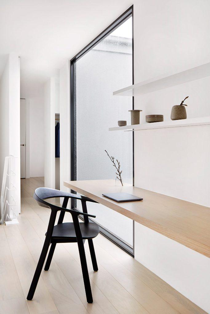 Le bureau à domicile montre des étagères ouvertes et un bureau flottant et il y a une grande fenêtre pour laisser entrer plus de lumière