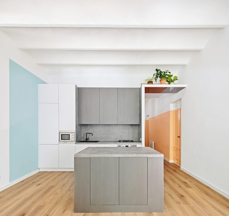 La cuisine présente également des blocs de couleurs avec des meubles gris graphite et un carré bleu clair