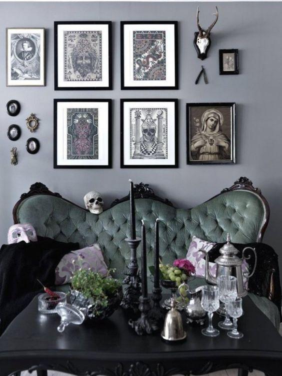 un salon gothique chic avec des murs gris, un canapé vert raffiné, une table noire et un mur de galerie accrocheur et des bougies