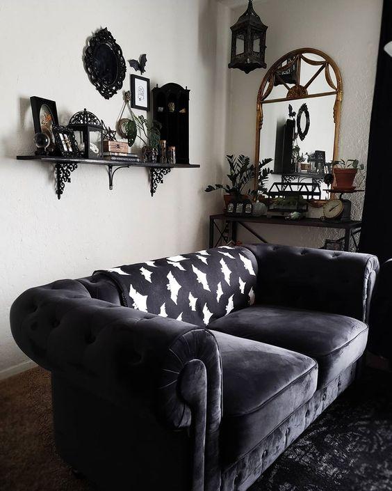 un salon gothique chic avec des murs blancs, des meubles sombres, une étagère avec des objets sympas exposés et de la verdure en pot