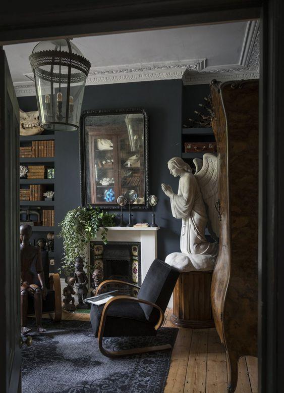 un salon gothique avec cheminée en faïence, moulures, mobilier noir, œuvres d'art uniques et verdure en pots