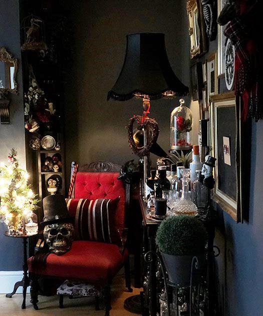 un salon gothique avec des murs noirs, une chaise rouge raffinée, des crânes et un mur de galerie chic est frappant