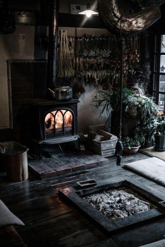 un espace gothique rustique avec un foyer vintage, un foyer, des plantes en pot et des sols noirs pour une sensation de sorcière