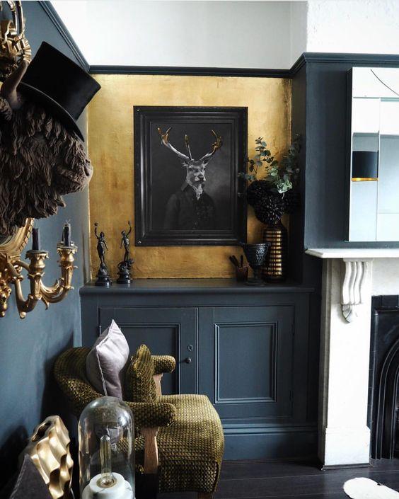 une salle de séjour gothique moderne et lumineuse avec des murs gris et or, une cheminée, des boiseries grises, des touches dorées et des œuvres d'art